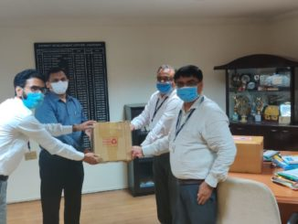 ICICI Bank officials handing over protective equipment to senior government official in Vadodara.